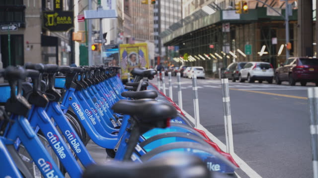 city bikes in docks on a street in downtown manhattan still unclaimed because of the absence of tourists and commuters caused by the coronavirus... - downtown stock videos & royalty-free footage