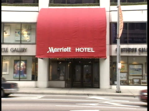 city building possibly marriott hotel td pan to ws marriott hotel entrance w/ red awning marriott hotel traffic on street fg - awning stock videos & royalty-free footage