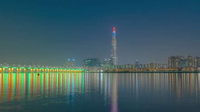 stockvideo's en b-roll-footage met city buildings near lotte world tower (skyscraper) and jamsildaegyo bridge at night / han river, seoul, south korea - straatnaambord