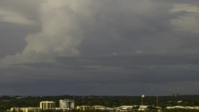 WS ZI T/L City buildings towards thunderstorm with lightning at dusk and night / Darwin, Northern Territory, Australia