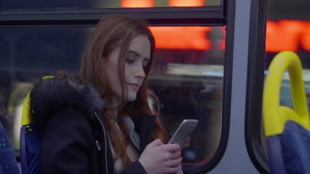 stockvideo's en b-roll-footage met stadsbus in de schemering, smartphone vrouw. - bus