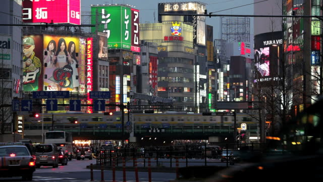 city centre road traffic, trains and commuters, shinjuku, tokyo city centre, japan, asia - eisenbahnwaggon stock-videos und b-roll-filmmaterial