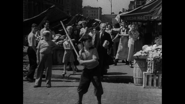 city children playing stickball on street buildings bg. boy batting w/ stick people in market watching bg. boys shooting craps. children playing... - craps stock videos & royalty-free footage