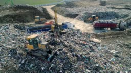 City Dump. The Bulldozer Moves Along the Landfill, Leveling the Garbage. Aerial View