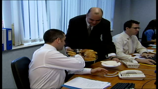 city firm lays on treats for staff; england: london: int i/c at desk at approached by masseuse and butler worker receiving massage butler serving... - masseur stock videos & royalty-free footage
