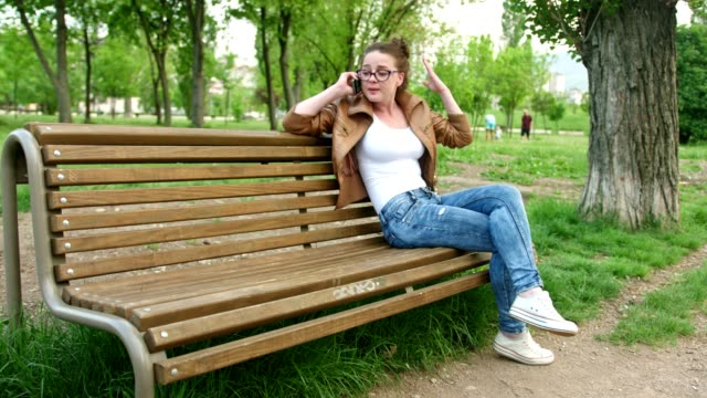 City girl sitting on a bench in the park and talking on her smart phone