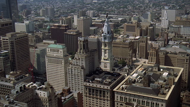 aerial city hall amongst other buildings in downtown philadelphia / philadelphia, pennsylvania, united states - local government building stock videos & royalty-free footage