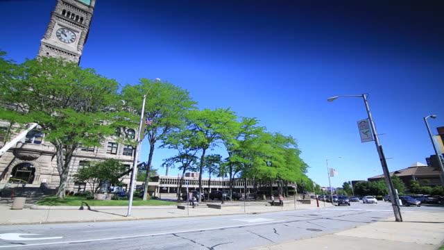 city hall building w/ clock tower unidentifiable people walking across sidewalk trees w/ green leaves street fg - lowell stock videos & royalty-free footage