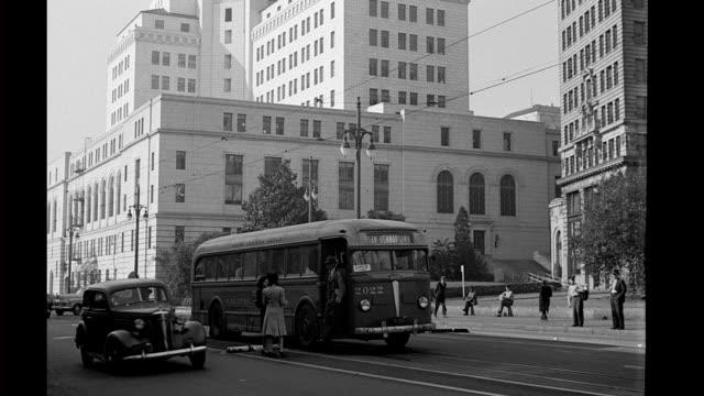 vídeos y material grabado en eventos de stock de city hall in background automobiles and buses passing in foreground city hall on january 01 1944 in los angeles california - edificio de ayuntamiento local