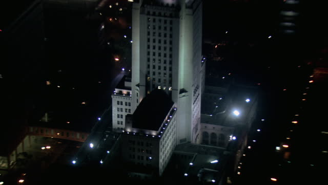 AERIAL City Hall lit by floodlights at night / Los Angeles, California, United States