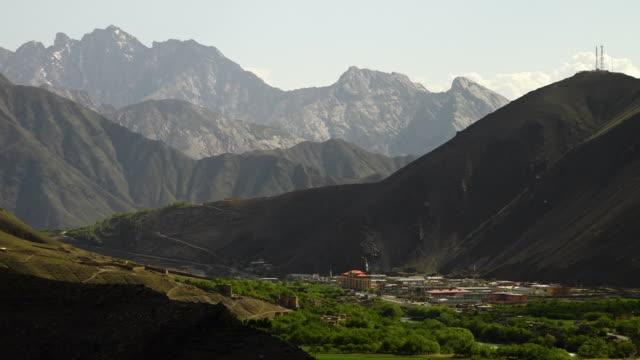 a city hidden by the mountains - umgeben stock-videos und b-roll-filmmaterial