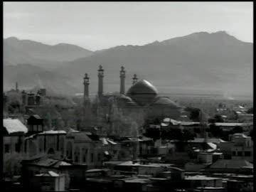 city in iran, masjid w/ mountains bg. toopkhaneh square w/ large building, pool, camels & cars on road - 1951 bildbanksvideor och videomaterial från bakom kulisserna