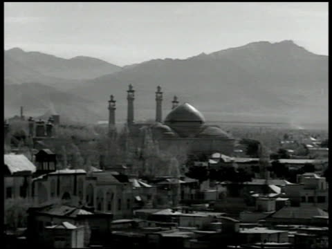 vídeos de stock, filmes e b-roll de city in iran, masjid w/ mountains bg. toopkhaneh square w/ large building, pool, camels & cars on road - 1951