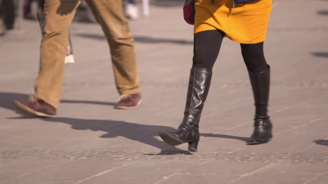 city, legs of a woman, woman wearing a skirt and boots