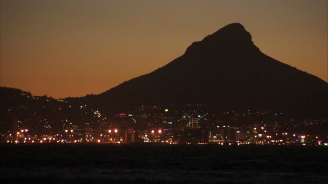 City lights glow at the base of Table Mountain in Cape Town.