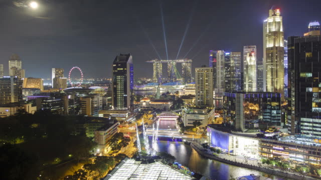 City lights illuminate the entertainment district of Clarke Quay and the Singapore river at night.