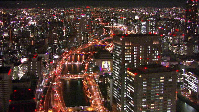 City lights twinkle along a river in Naka-no-Shima, Japan. Aerial Shot