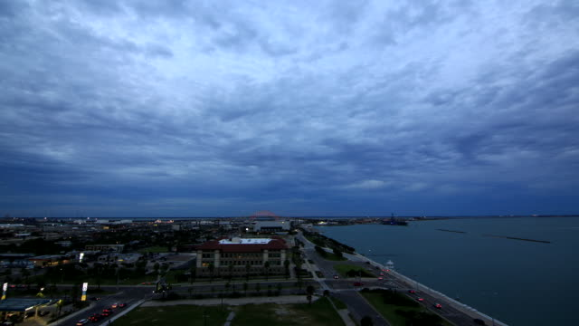 vidéos et rushes de city lowrise buildings next to corpus christi bay rapid motion vehicles driving along streets clouds moving across sky lights changing on harbor... - rapid city