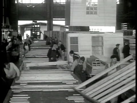 stockvideo's en b-roll-footage met city lumber company w/ men driving machine carrying lumber int warehouse w/ men working on prefab house frames male placing plumbing pipes working on... - 1946