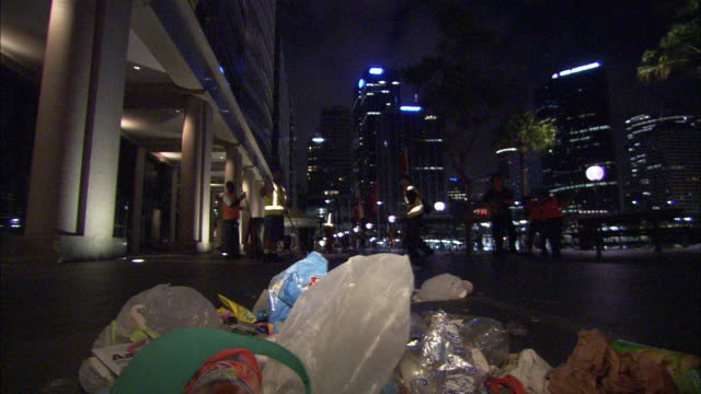 A city maintenance crew sweeps trash from a street in Sydney.
