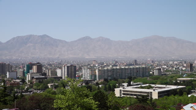 a city near the mountains - umgeben stock-videos und b-roll-filmmaterial