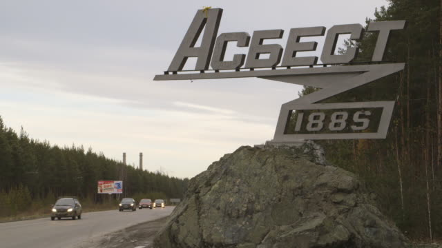 city of asbest welcome sign on highway, cars pass on highway - asbest stock-videos und b-roll-filmmaterial