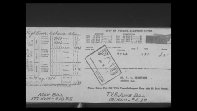 stockvideo's en b-roll-footage met cu city of athens alabama electric bill with paid stamped on it / cu hand signs tax return / cu hand signs check - financieel item