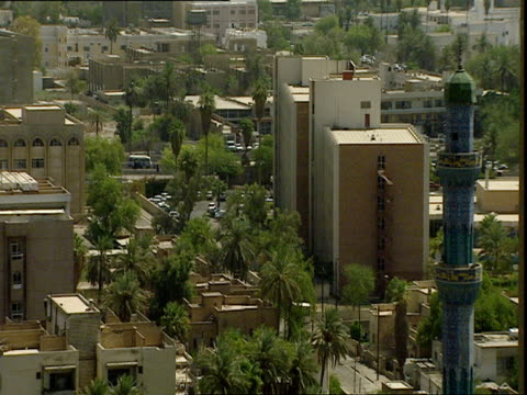 city of baghdad with minaret, apartment buildings and palm trees / baghdad, iraq - baghdad stock videos & royalty-free footage