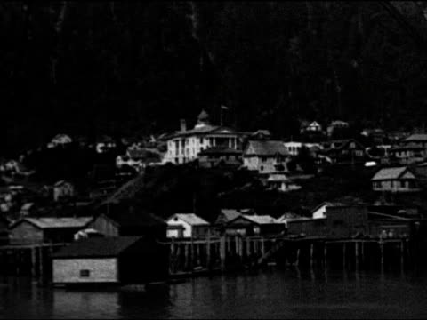 ls of city of juneau from harbor with mountain in background / tracking shot along shore front with fishing camps / pan across town from above... - juneau stock videos and b-roll footage