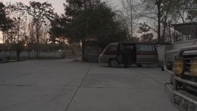 city of kabul - wide shot of a parked van, men getting stuff from car - kabul stock videos & royalty-free footage