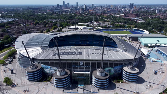 city of manchester stadium (known as the etihad stadium.) city skyline behind.rising drone shot. - tracking shot stock videos & royalty-free footage
