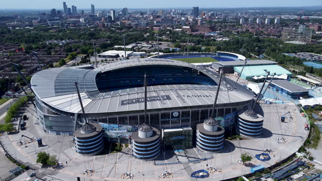 city of manchester stadium (known as the etihad stadium.) city skyline behind.tracking shot. - video stock videos & royalty-free footage