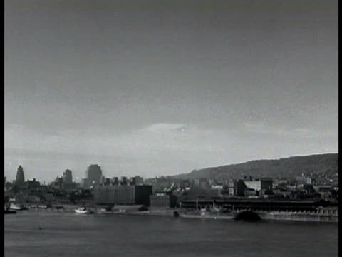 city of montreal w/ river fg. montreal riverfront. train rail freight yard locomotives moving freight cars standing on tracks. - 1943 stock-videos und b-roll-filmmaterial