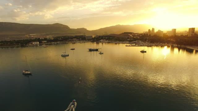 veduta aerea della città sulla costa al tramonto - canottaggio senza timoniere video stock e b–roll