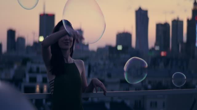 vídeos de stock, filmes e b-roll de panorama da cidade que reflete em bolhas de sabão. fêmea que paquera com câmera - espuma