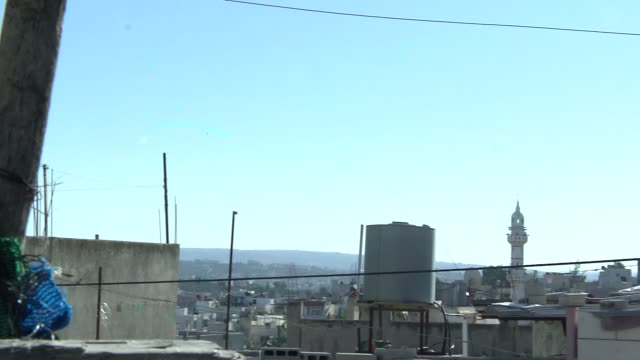 city panorama with palestinian flag waving in the wind - palestinian flag stock videos & royalty-free footage