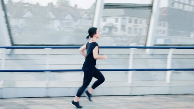 city runner: young asian woman running on pedestrian bridge in city - competition stock videos & royalty-free footage