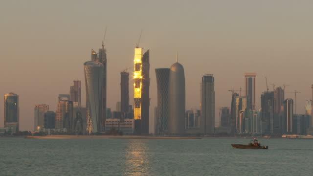 ws city skyline across doha bay at sunset / doha, qatar - doha stock videos & royalty-free footage