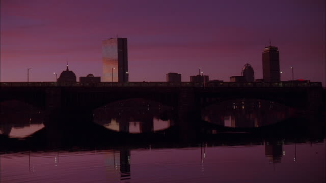 la city skyline against a sunset, reflected in still water with an elevated train passing / massachusetts, united states - establishing shot点の映像素材/bロール