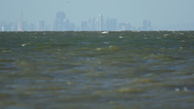 city skyline beyond quiet waves of bay - water's edge stock videos & royalty-free footage