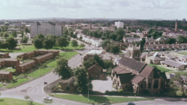 1980 pan city skyline, businesses, and residences with traffic and semi-detached suburban housing development / birmingham, england, united kingdom - doppelhaus stock-videos und b-roll-filmmaterial