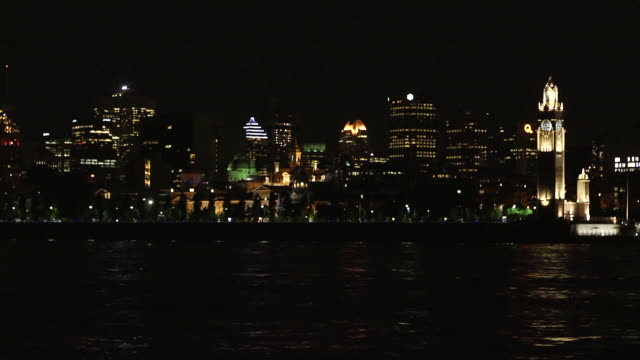 WS City skyline mid highrise buildings skyscrapers clock tower lights reflecting in Saint Lawrence River FG
