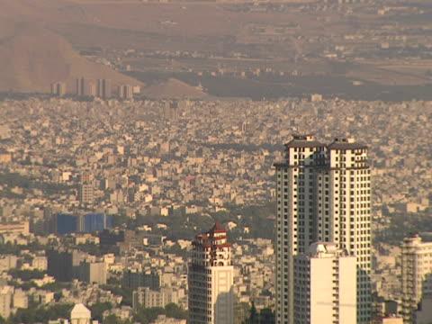 vídeos y material grabado en eventos de stock de selective focus city skyline of skyscrapers towering over landscape of urban sprawl / tehran, iran - formato buzón