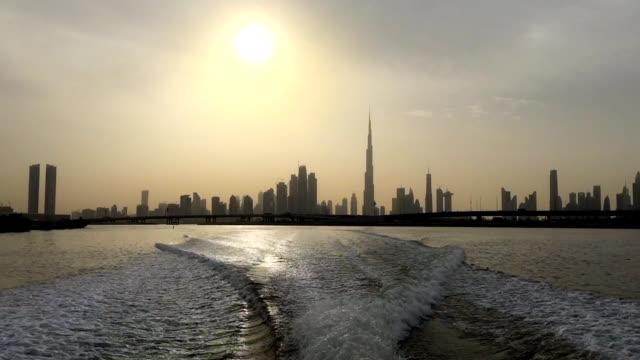 vidéos et rushes de toits de la ville de bateau quittant le sentier sur la surface de l'eau - au loin