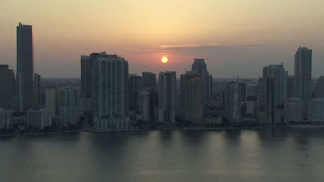 ws city skyline skyscrapers highrise buildings biscayne bay fg orange sun in sky bg zi/zo urban cityscape - san francisco bay stock videos & royalty-free footage
