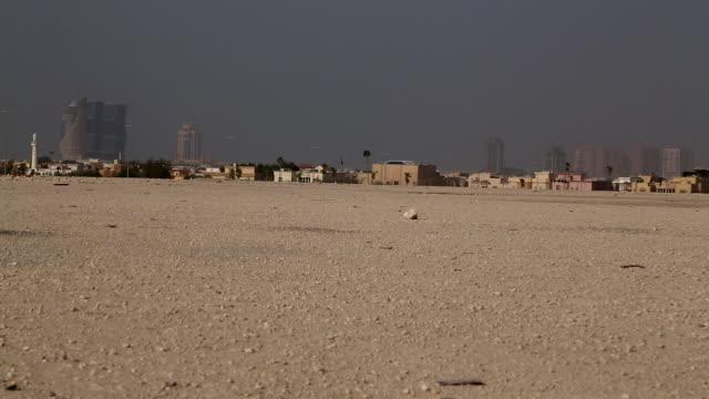 xws city skyline skyscrapers lowrise buildings in fog smog empty flat brown/beige desert landscape fg - qatar stock videos & royalty-free footage
