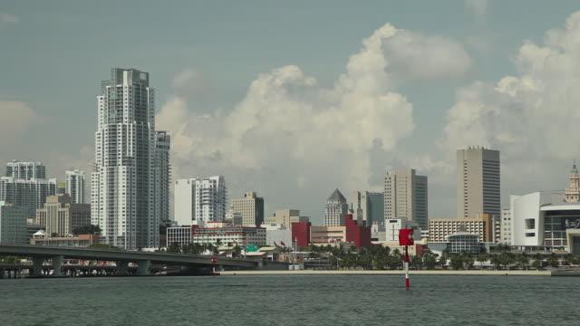 City skyline skyscrapers vehicles driving across Port Boulevard highway bridge Biscayne Bay blue sky w/ white clouds