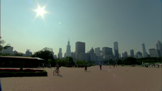 ws city skyline skyscrapers willis tower bright sun in blue sky unidentifiable people walking riding bicycles pan to clarence f buckingham memorial... - willis tower stock videos & royalty-free footage