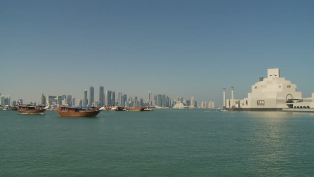 ws city skyline with museum of islamic art seen across doha bay / doha, qatar - doha bildbanksvideor och videomaterial från bakom kulisserna