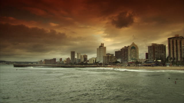 ws city skyline with people swimming at beach in foreground / durban, kwazuzlu natal, south africa - durban stock videos and b-roll footage